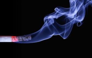 a cigarette releasing a plume of smoke