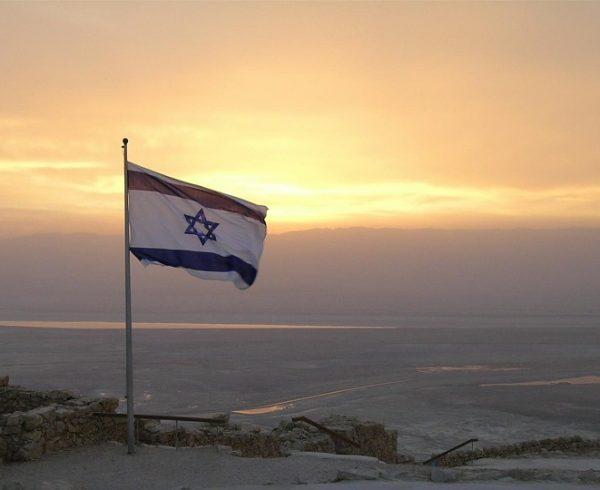 Flag of Israel on sunset background.