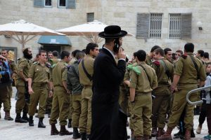Orthodox Jewish man looking at soldiers in Israeli city. After moving to Israel, take extra care of your security.