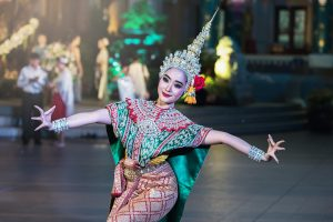 A woman in traditional Thai clothes during a festival you can visit when moving to Asia.