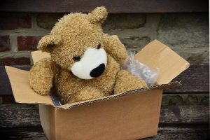 a box with stuffed bear toy in it