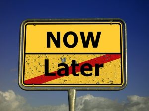 """Sign with written """"now"""" and crossed word """"later""""."""