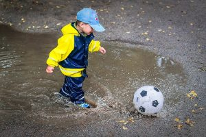 A boy playing football in mud.