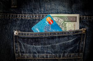 Back pocket of jeans with credit card and money sticking out