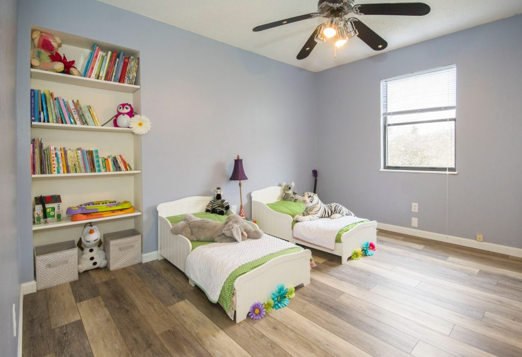 Kids' room with two little beds and a bookcase.