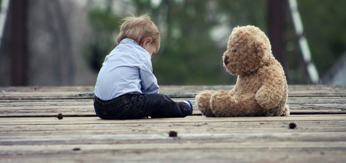 A baby boy sitting on a wooden bridge next to a large teddy bear.