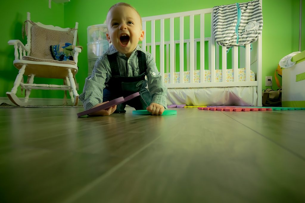 A toddler playing on the floor in a nursery.