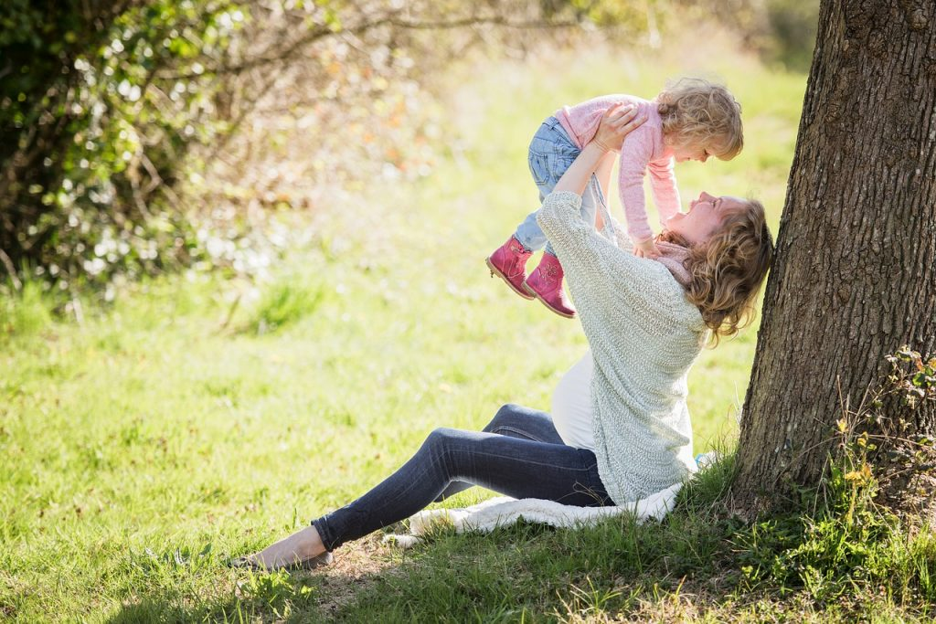 A mother plays with her little girl in a park.