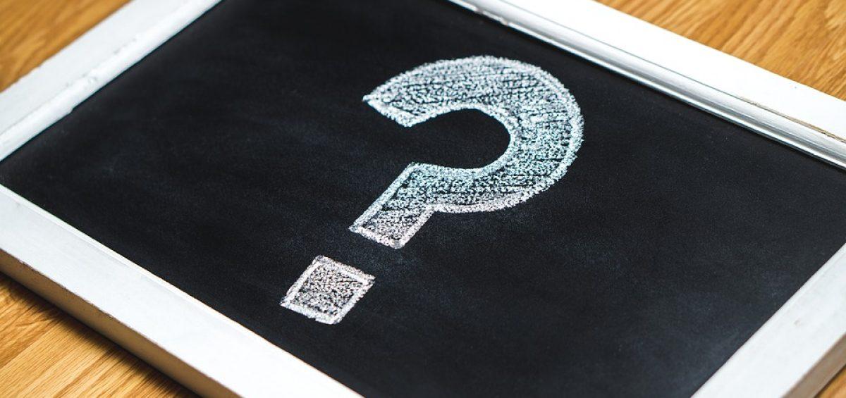 a white question mark written on a black board