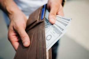 a man holding a wallet filled with 100 dollar bills