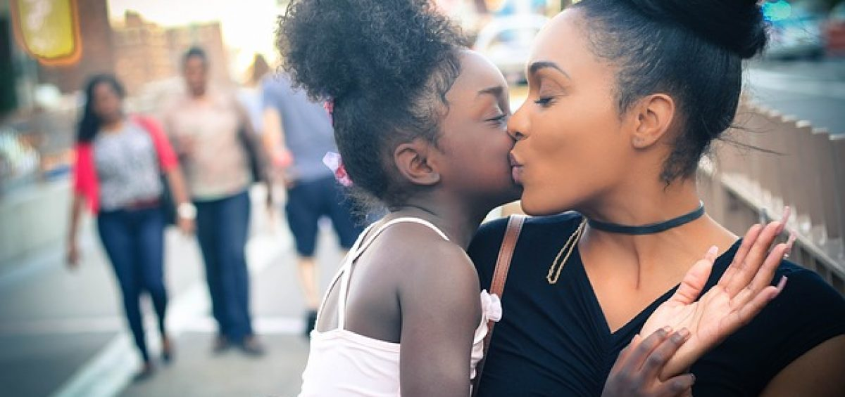 mother kissing her little girl probably prior to moving to Raleigh