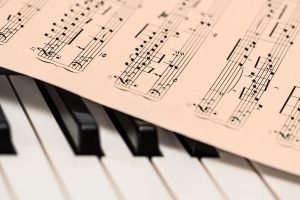 Some musical notes placed on the keys of a piano.