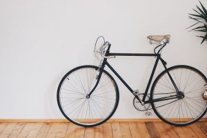 A bicycle leaned on the white wall because you need to prepare enough space to prepare a bicycle for moving.