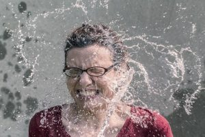 A woman aggressively splashed by water.