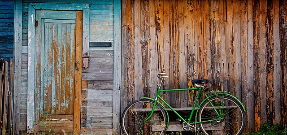 A bike next to an old shed.