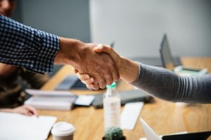 A male and a female shaking hands in an office.