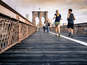 A Man and A Woman in sports gear runing across Brooklyn Bridge in daytime.