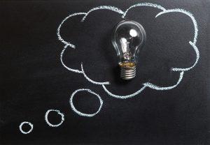 A lightbulb in a chalk-drawn cloud on a black board.