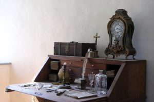 An antique desk, a clock and some details.