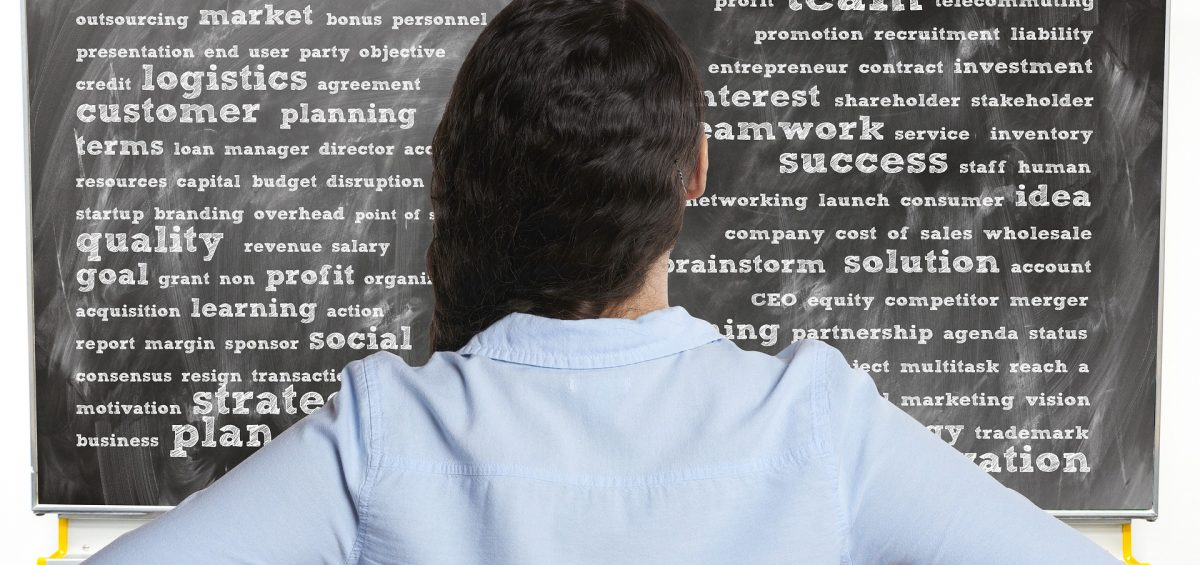A women looking at a board of business key words.