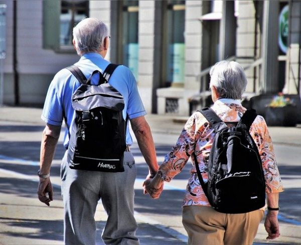 An elderly couple walking hand in hand and discussing the best retirement spots in Florida.