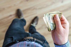 Man holding ten dollar bills.