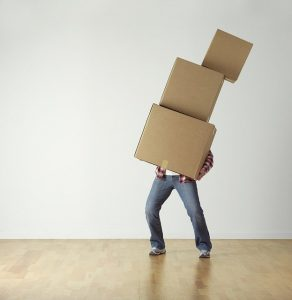 A man carrying a pile of moving boxes as you will do while trying to speed up your moving in process.