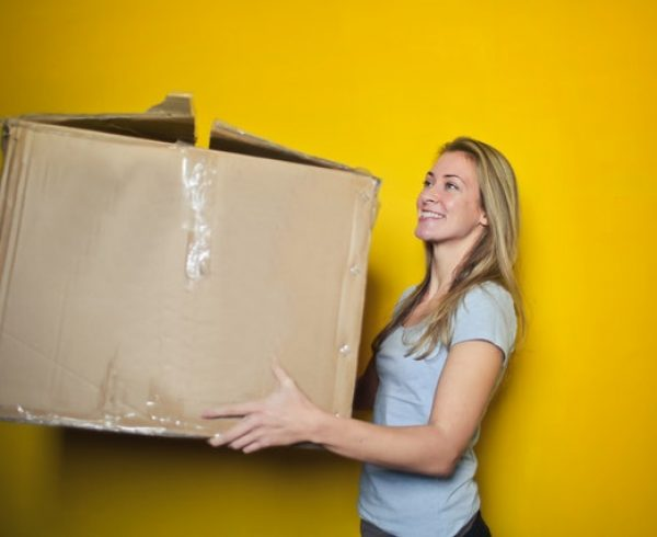 A woman who knows how to save money on packing supplies carrying a cardboard box.