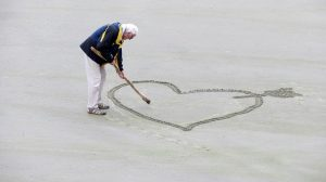 Man drawing a heart on the beach and thinking about the best places to retire in Pinellas County.