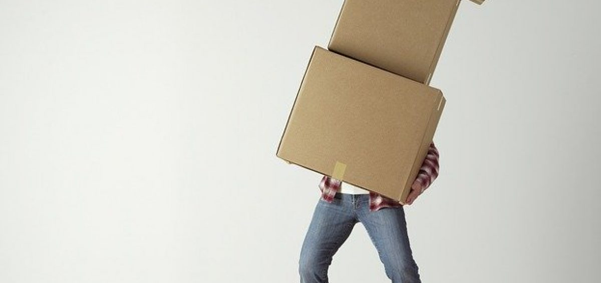 A man carrying a pile of cardboard boxes while moving to Hilliard.