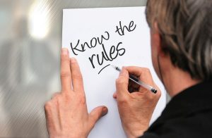 """A man writing """"know the rules"""" sentence on the paper."""