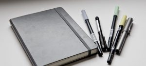 A black journal and pens. By creating a plan, you can use it for staying organized on a moving day.