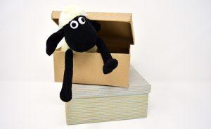 A sheep toy in a cardboard box.
