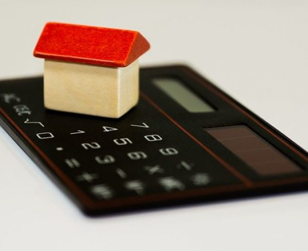 A small wooden house on a calculator symbolizing the budget for moving to Queens