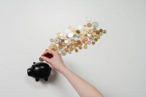 A person putting coins into a piggy bank.