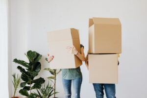 man and woman holding moving boxes