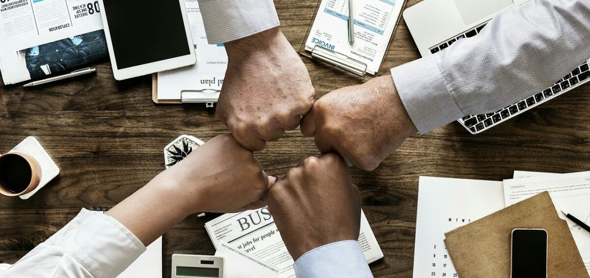 Colleagues making a fist bump at their office.
