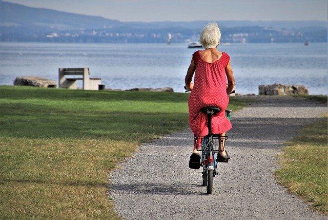A senior woman riding a bike.