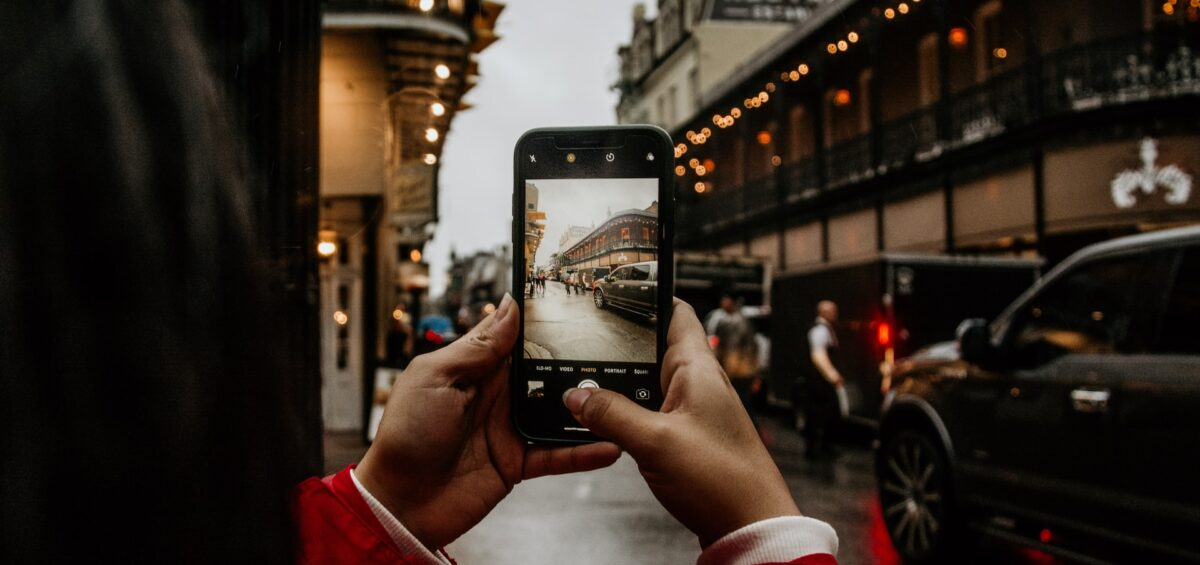 A man taking a photo of a street in New Orleans, one of the Lousiana places that will take your breath away.
