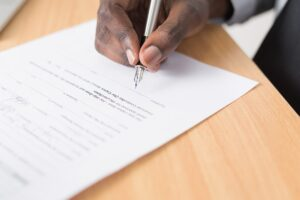A hand signing a contract.