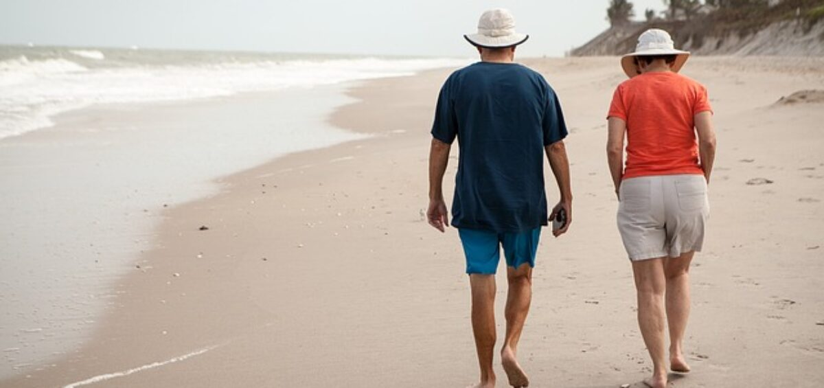 An older couple is walking on the beach and they are looking for one of the best senior-friendly cities in California.
