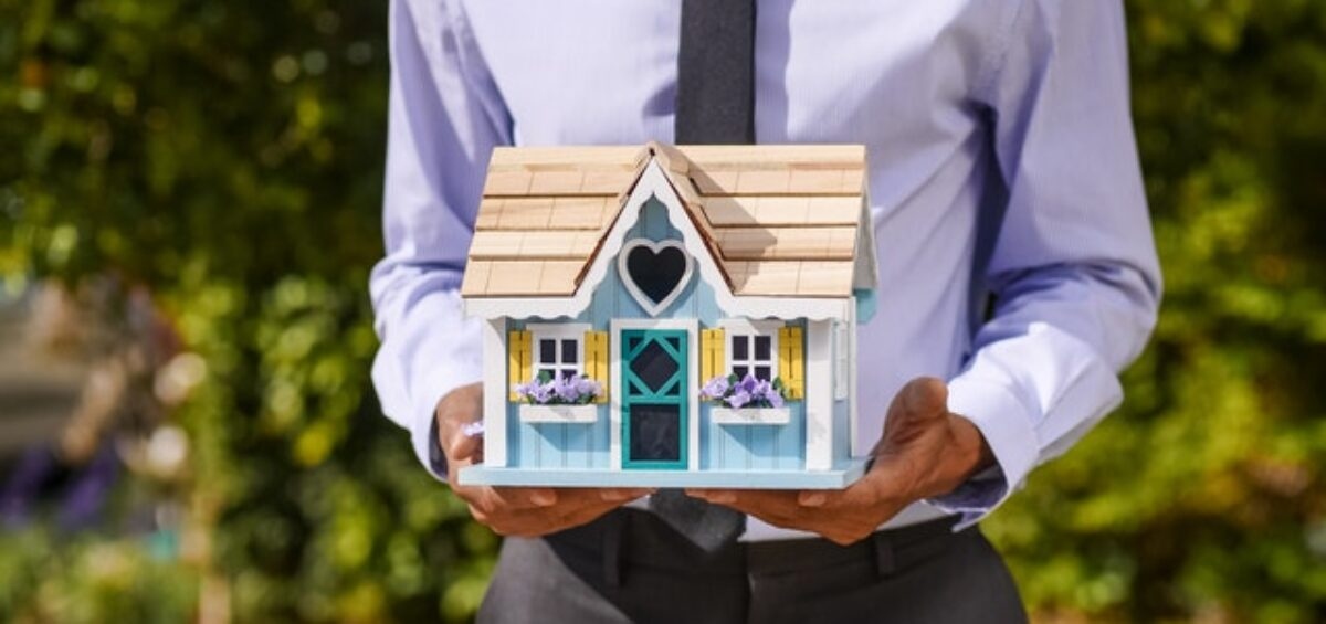 a man in a suit holding a wooden house