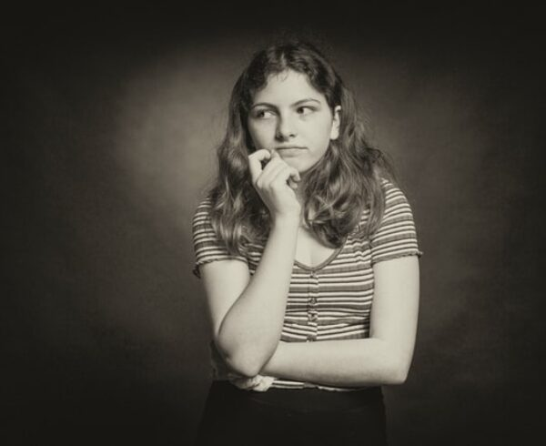 A black and white photo of a girl in a striped T-shirt thinking about moving to Boerum Hill