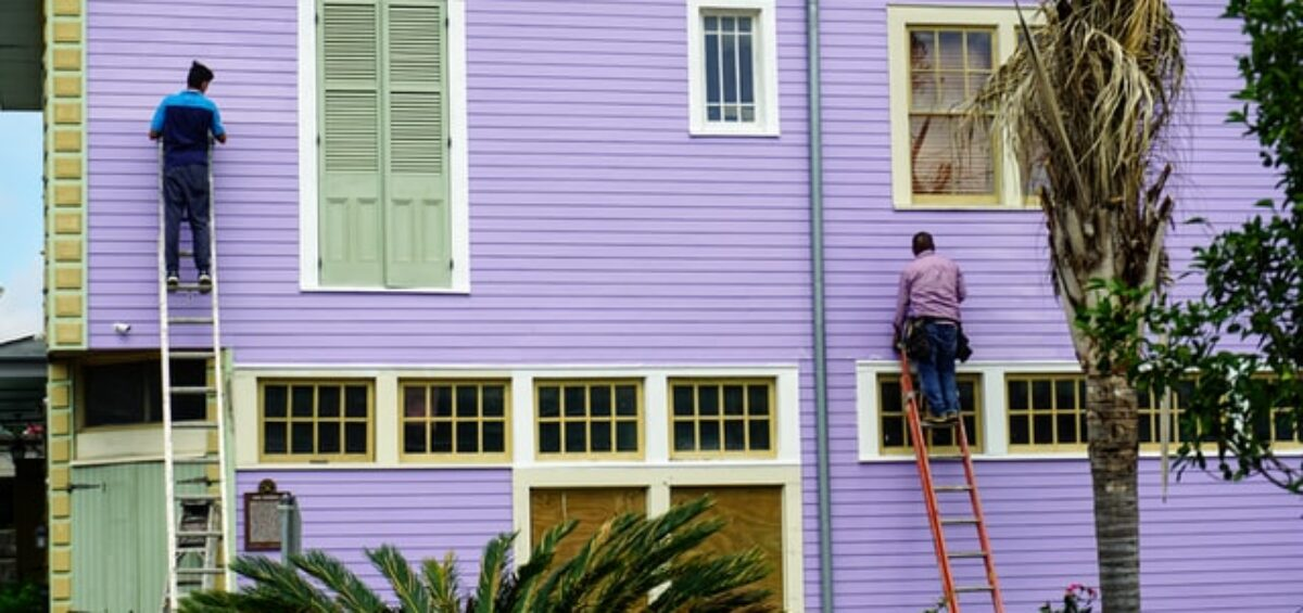 Two people on latter painting the house purple, read about household repairs before selling