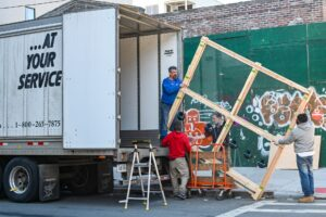 Professional movers loading a moving truck as one of the best tips for gallery owners is to hire movers